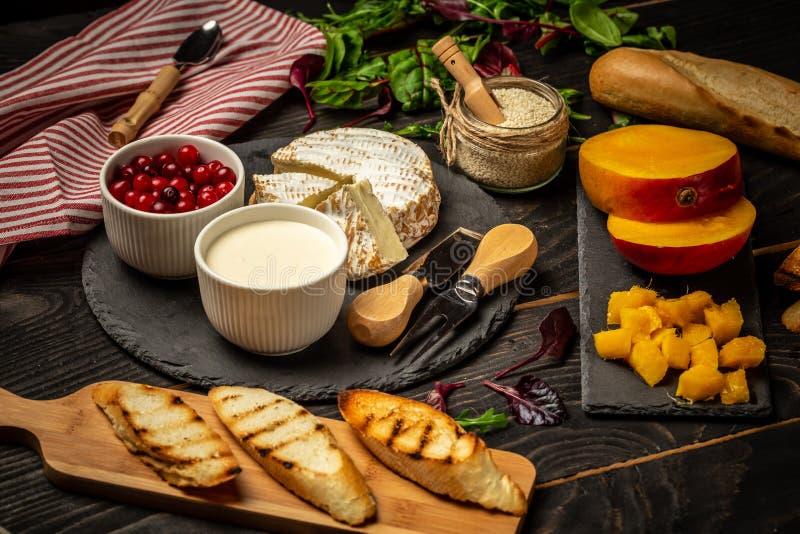 烹调意大利食物 新鲜食品成份品种多士的与Bruschetta用切好的芒果,在新鲜的奶油奶酪 免版税库存照片