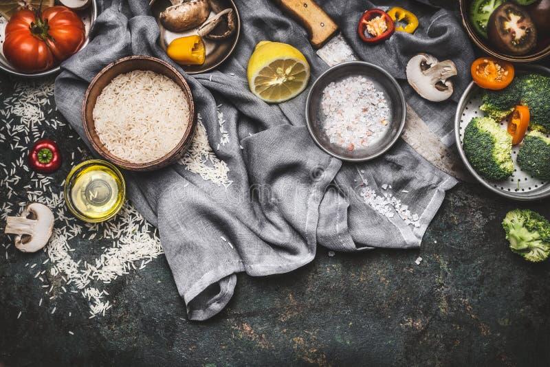 烹调成份用柠檬、米和菜的素食主义者在黑暗的土气背景,顶视图,边界 健康或饮食食物 免版税库存图片