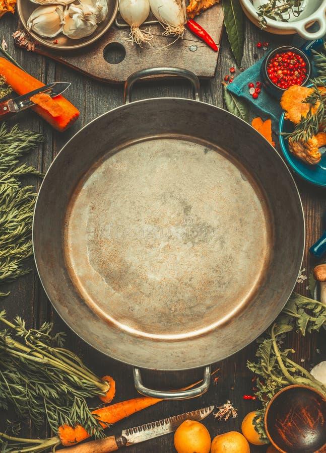 烹调成份的素食主义者在空白附近变老了烹调在黑暗的土气厨房用桌,顶视图上的罐 免版税库存照片