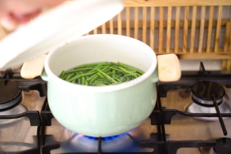 烹调新鲜的绿豆的年轻人 免版税图库摄影