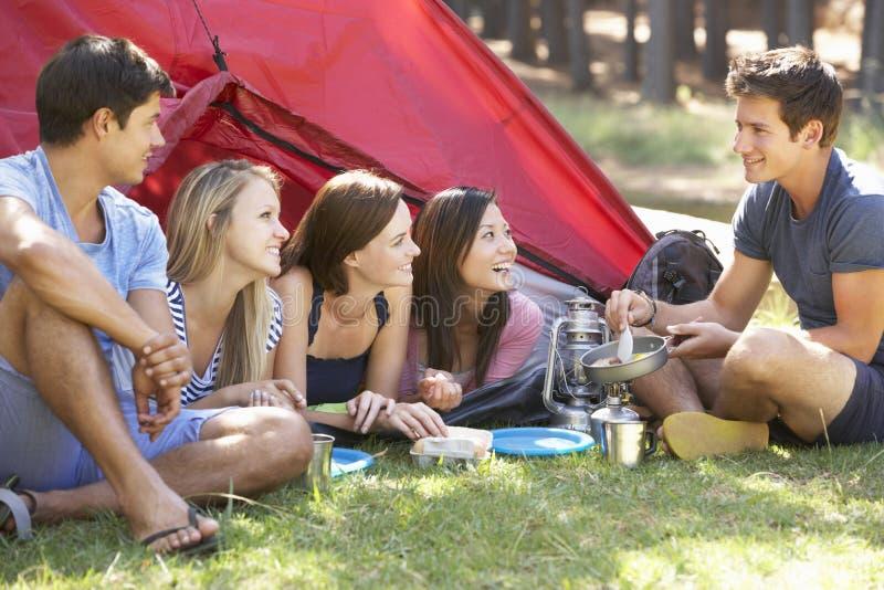 烹调早餐的小组青年人野营假日 免版税库存图片