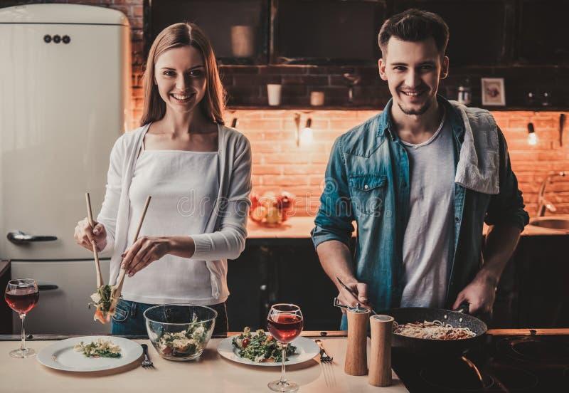 烹调晚餐和饮料红葡萄酒的年轻夫妇 免版税库存照片