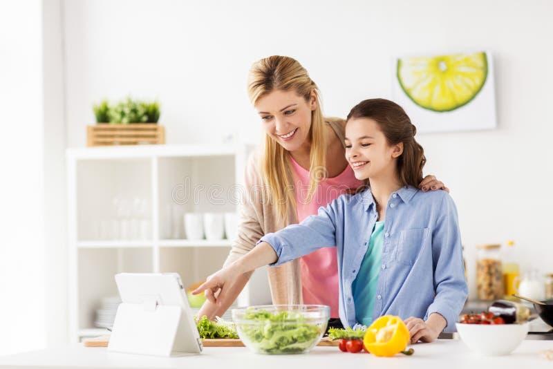 烹调晚餐的家庭使用片剂个人计算机在厨房 免版税库存照片