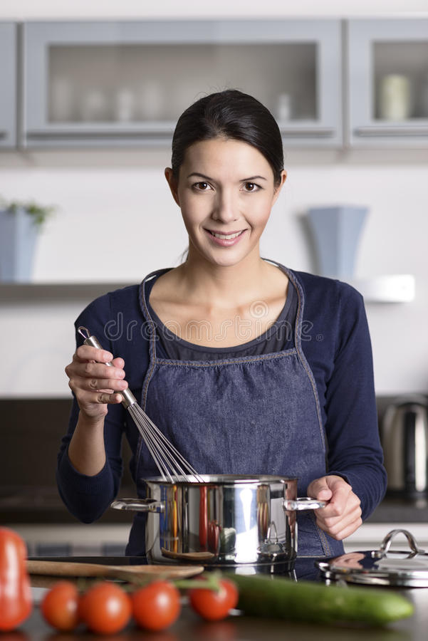 烹调晚餐的愉快的友好的年轻主妇 图库摄影
