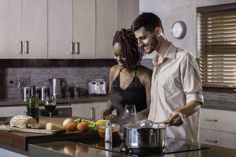 烹调晚餐的愉快的年轻混合的族种夫妇准备食物在厨房里 免版税库存图片