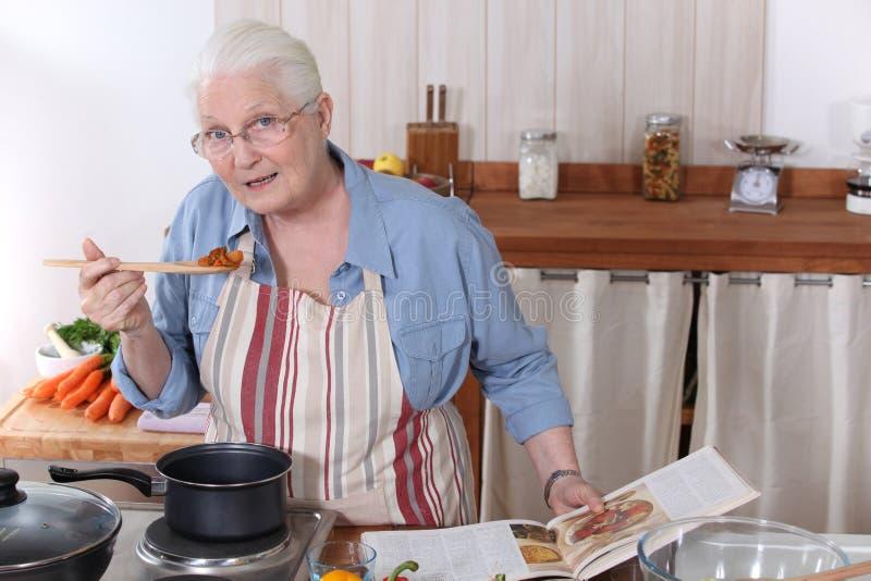 烹调晚餐的年长妇女 库存照片