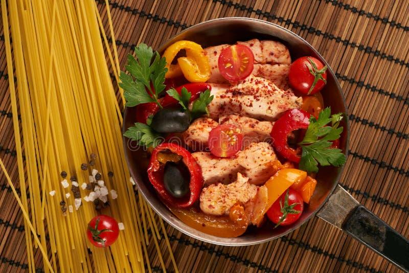 烹调有炸鸡内圆角和被烘烤的菜的平底锅 库存图片
