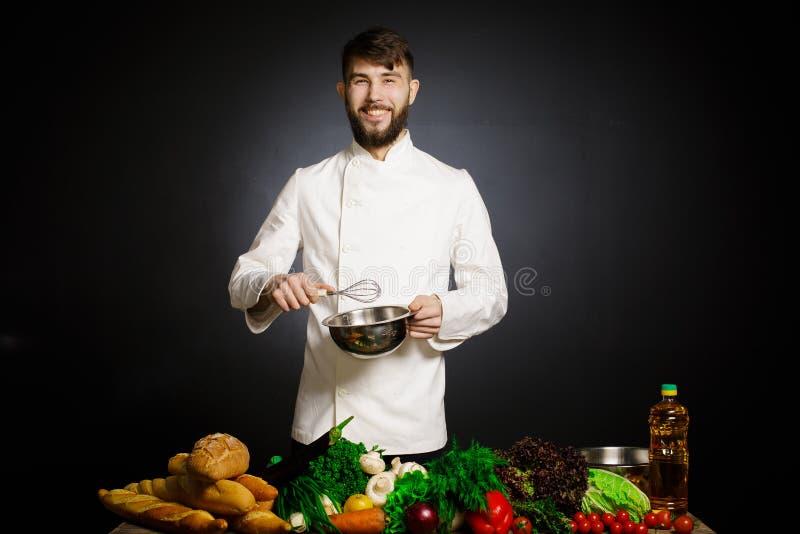 烹调有菜splah和黑黑暗的背景的厨师 食物音乐和谐 玩杂耍与菜和其他食物的厨师在t 库存照片