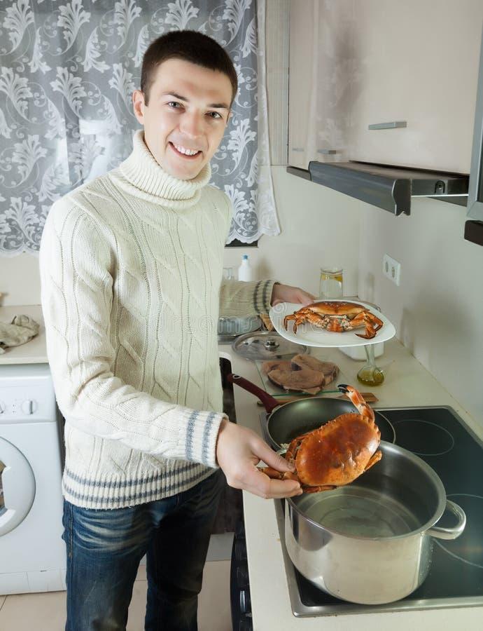 烹调未加工的螃蟹的英俊的人 免版税库存图片