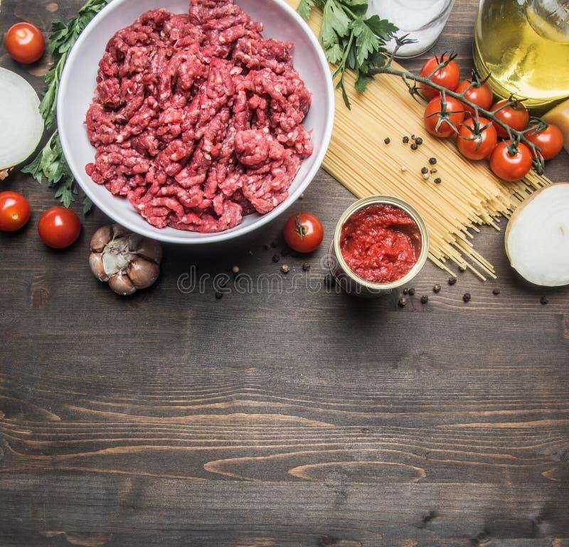烹调概念,未加工的肉末,西红柿酱,西红柿,面团,葱,大蒜,草本草本,油的博洛涅塞面团和ho 免版税库存图片