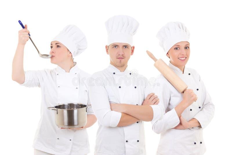烹调概念-在白色隔绝的三位年轻厨师 库存图片