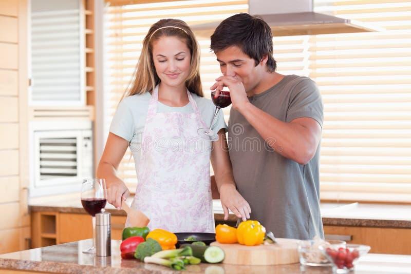 烹调正餐的新夫妇,当喝红葡萄酒时 库存图片