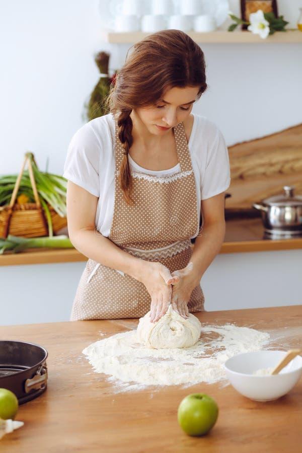 烹调比萨或手工制造面团的年轻深色的妇女在厨房里 准备在木桌上的主妇面团 ?? 免版税库存图片