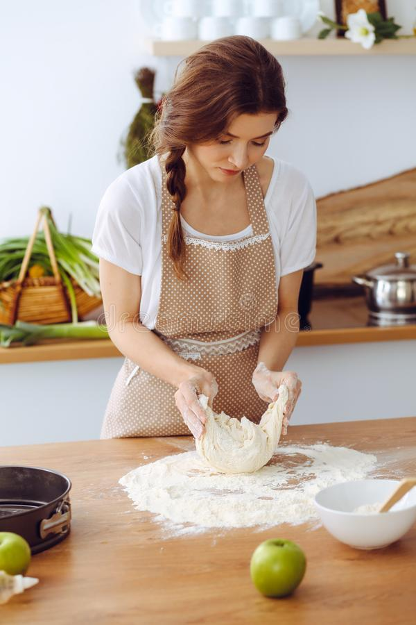 烹调比萨或手工制造面团的年轻深色的妇女在厨房里 准备在木桌上的主妇面团 ?? 免版税库存照片