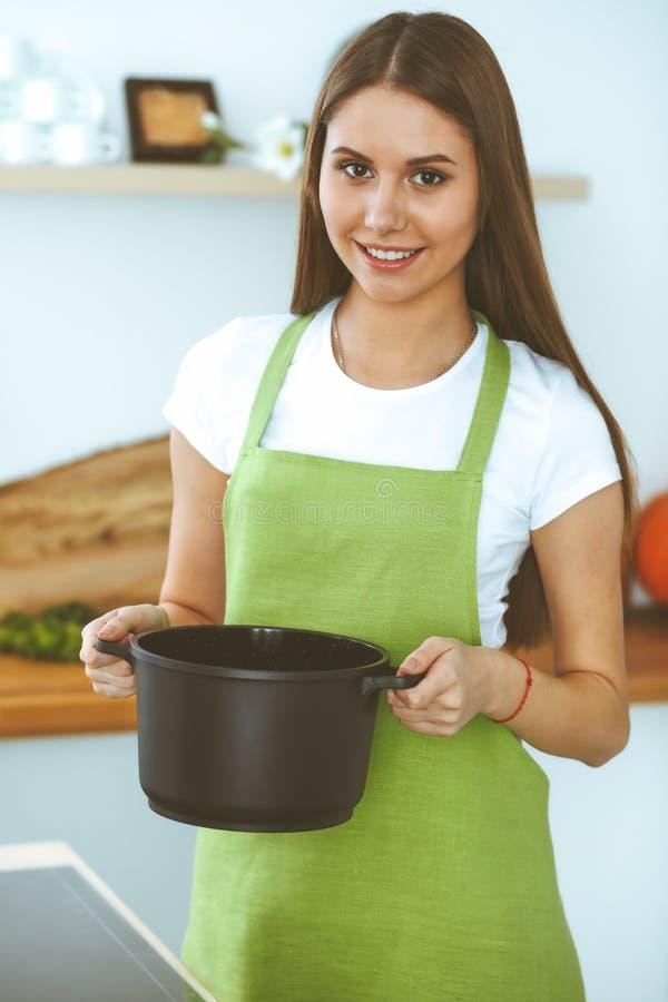 烹调汤的年轻愉快的妇女在厨房里 健康膳食、生活方式和烹饪概念 微笑的学生女孩 免版税库存图片