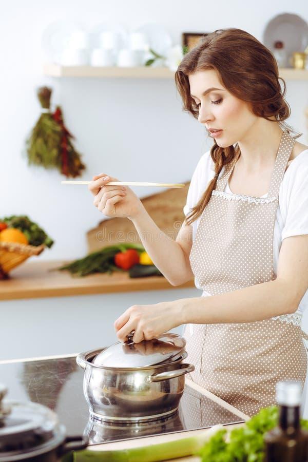 烹调汤的年轻深色的妇女在厨房里 主妇在她的手上的拿着木匙子 o 库存图片