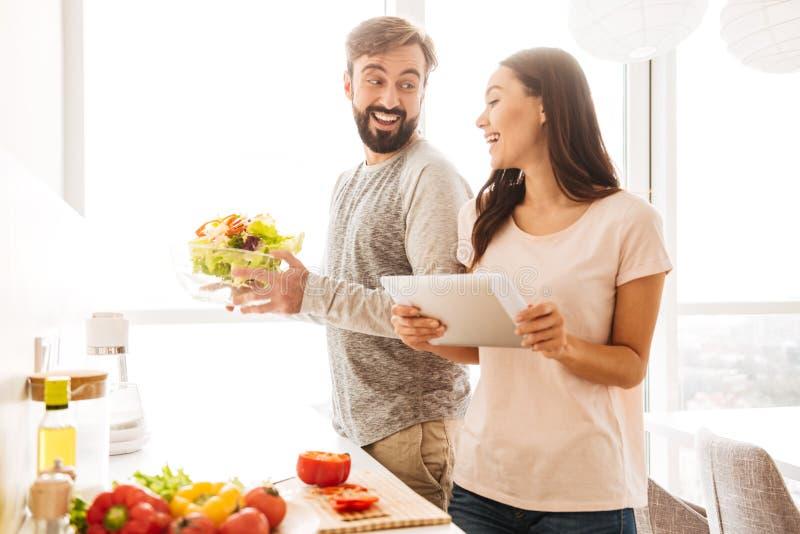 烹调沙拉的一对快乐的年轻夫妇的画象 免版税库存照片