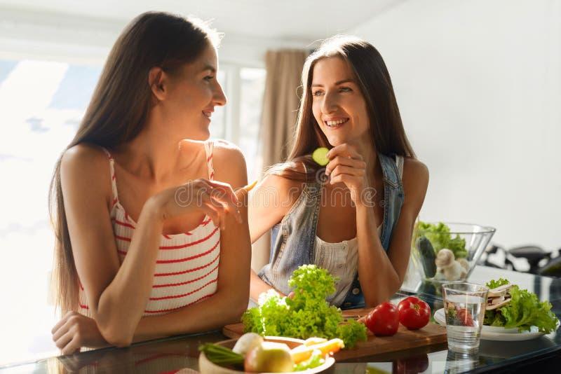 烹调沙拉的健康吃的妇女在厨房里 健身饮食食物 免版税库存图片