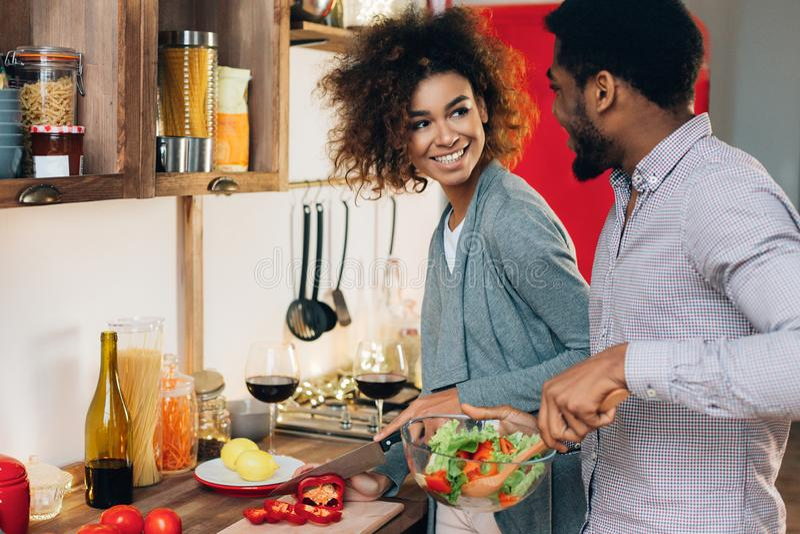 烹调沙拉的素食非裔美国人的夫妇在厨房里 免版税图库摄影