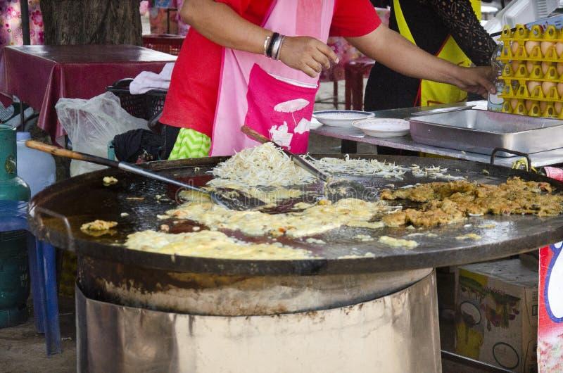 烹调油煎的淡菜用鸡蛋和酥脆面粉或者牡蛎煎蛋卷的泰国人待售在市场上在信武里,泰国 库存图片