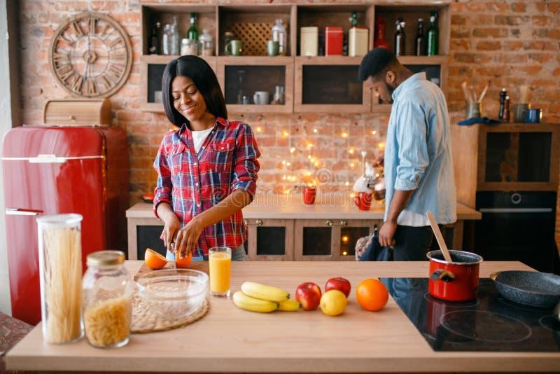 烹调浪漫晚餐的黑爱夫妇 库存照片