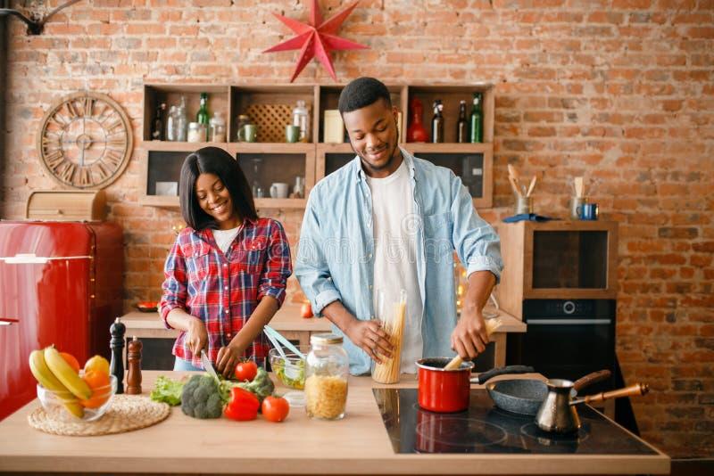 烹调浪漫晚餐的黑爱夫妇 库存图片