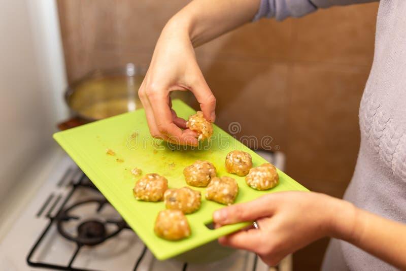 烹调火鸡丸子的妇女在厨房里 免版税库存照片