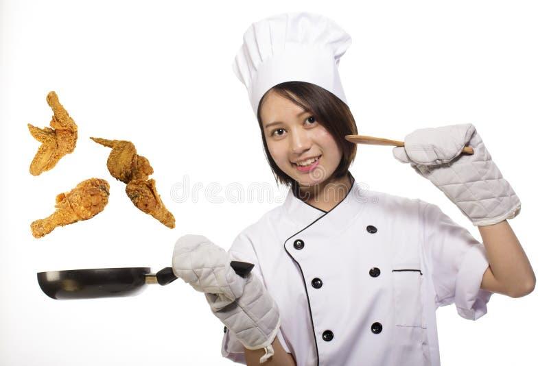 烹调炸鸡的年轻亚裔女孩 免版税库存图片