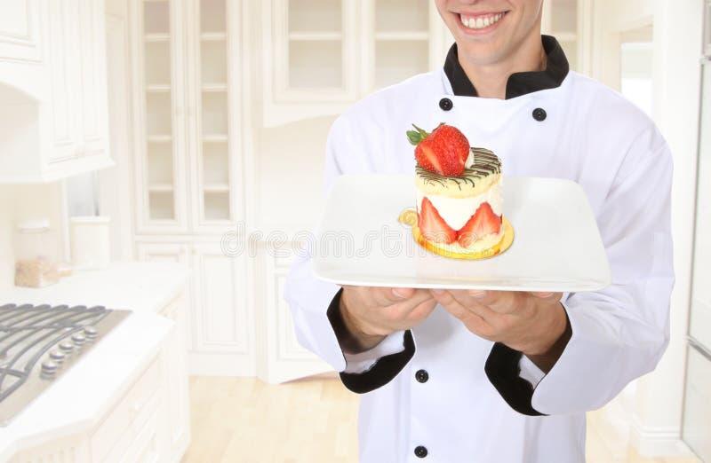 烹调点心的主厨愉快 免版税库存图片