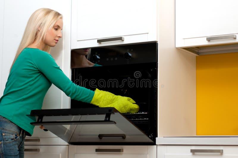 烹调烤箱妇女年轻人 库存照片