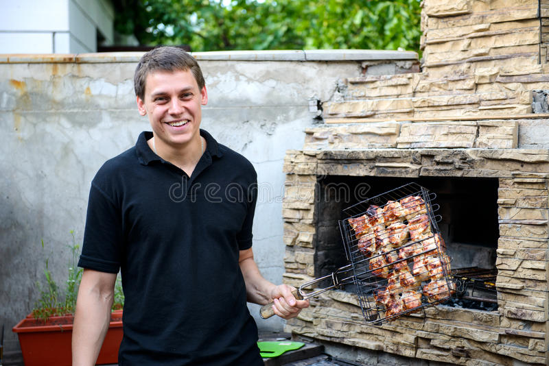烹调烤肉的愉快的人 免版税图库摄影