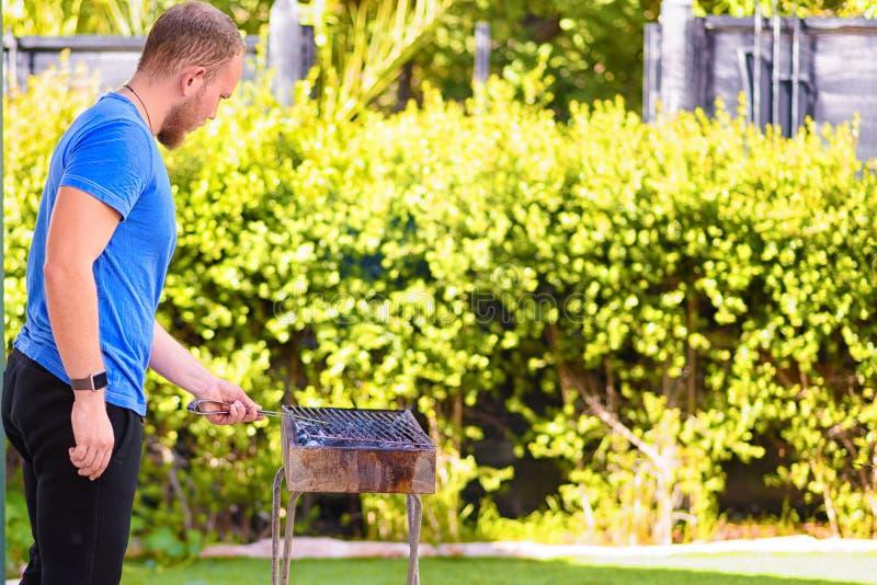 烹调烤肉的英俊的残酷有胡子的人户外 免版税库存照片