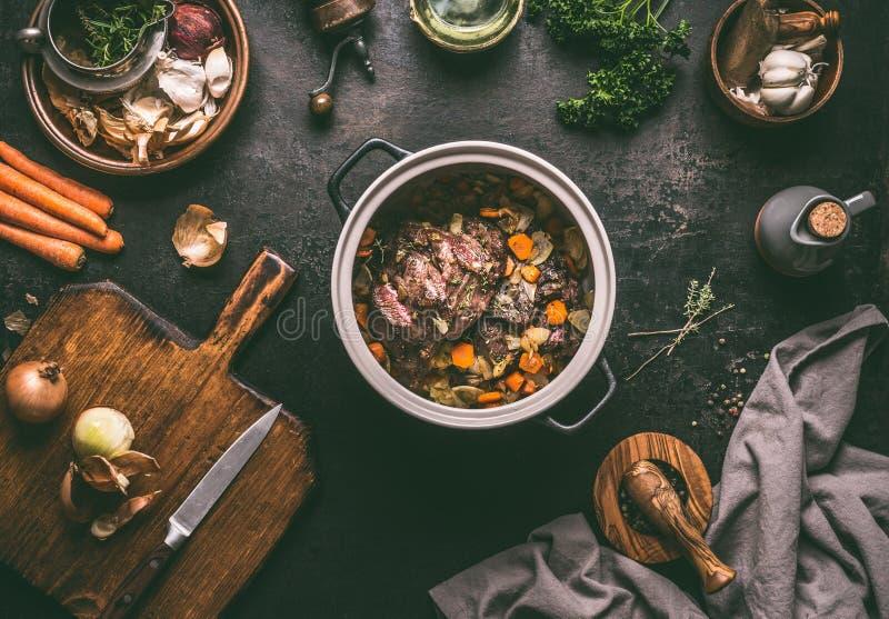 烹调焖肉的准备 在烹调有菜的生铁的烤牛肉肉罐在黑暗的土气背景与 图库摄影