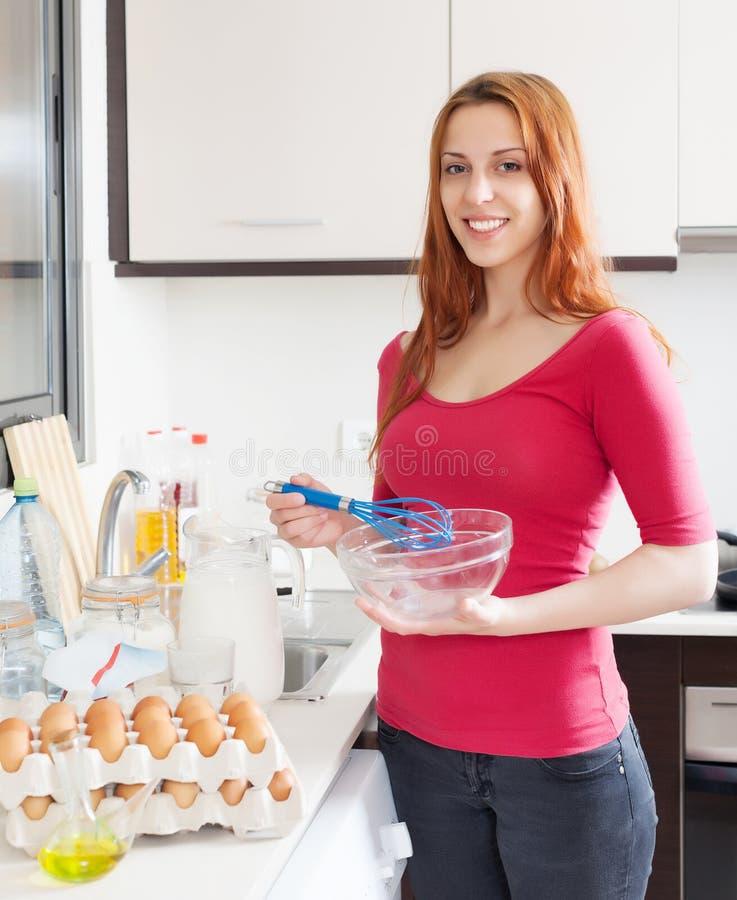 烹调煎蛋卷的微笑的妇女 免版税库存图片