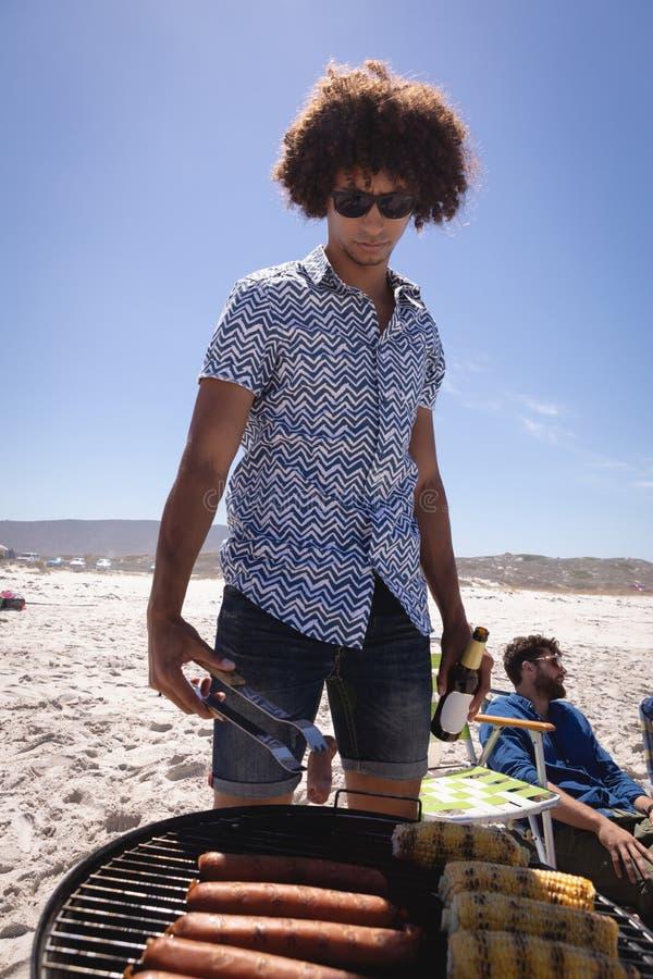 烹调玉米和香肠在烤肉的年轻人在海滩在阳光下 免版税库存照片