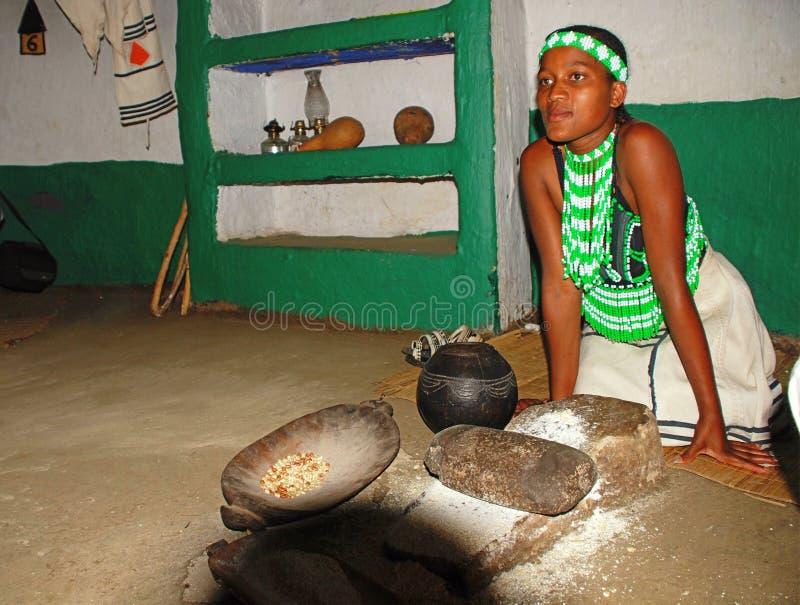 烹调玉米膳食的祖鲁族人妇女在部族房子, Lesedi村庄 图库摄影