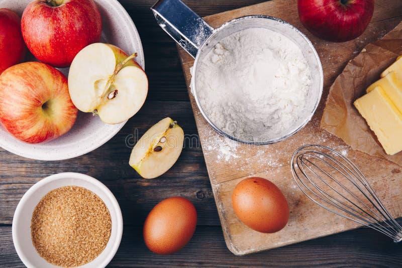烹调用新鲜的红色苹果、黄油、面粉、鸡蛋、红糖和香料的苹果饼的成份 图库摄影