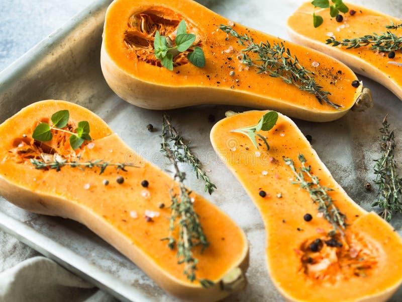 烹调用香料和草本的橙色新鲜的南瓜 削减在烤板的南瓜切片 新鲜的橙色麝香葡萄金瓜切成了两半,关于 免版税库存照片
