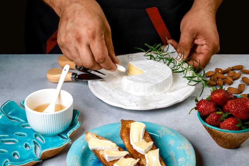 烹调由厨师手- bruschetta三明治用草莓,在烤面包的乳酪软制乳酪 库存图片