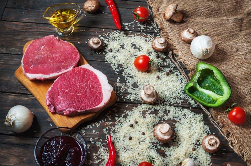 烹调的健康肉晚餐成份 未加工的未煮过的牛肋骨眼睛牛排用蘑菇、米、草本和香料在桌后面 库存图片
