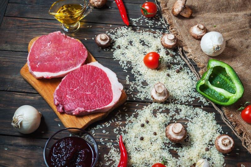 烹调的健康肉晚餐成份 未加工的未煮过的牛肋骨眼睛牛排用蘑菇、米、草本和香料在桌后面 免版税库存照片