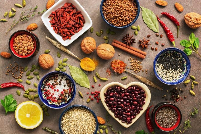 超级食物背景,各种各样的谷物,豆类,香料,草本,坚果 烹调的各种各样的调味料在棕色背景 ?? 库存照片