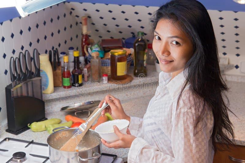 烹调的妇女在厨房里 库存照片