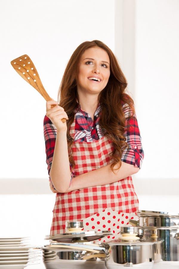 烹调的妇女,拿着厨房器物和罐 免版税图库摄影