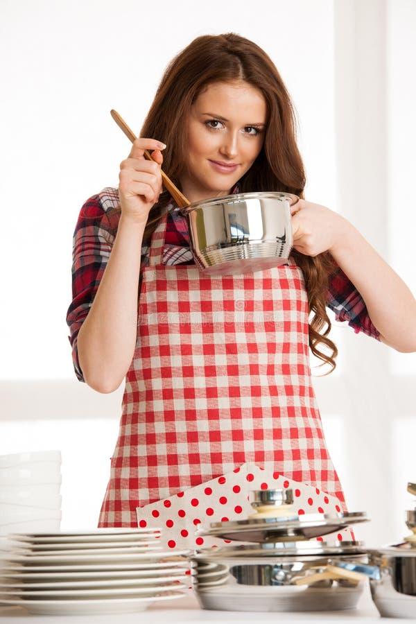 烹调的妇女,拿着厨房器物和罐 库存图片