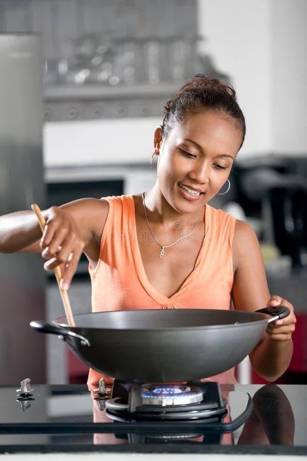烹调的年轻女人在家,准备食物 库存图片