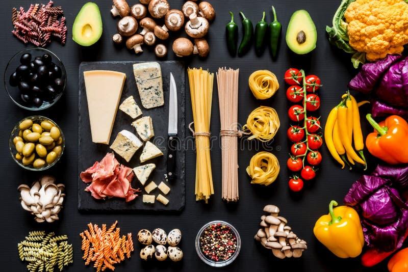 烹调的意大利面团、意粉、意大利细面条、fusilli和菜不同的新鲜的成份在黑色 免版税库存照片