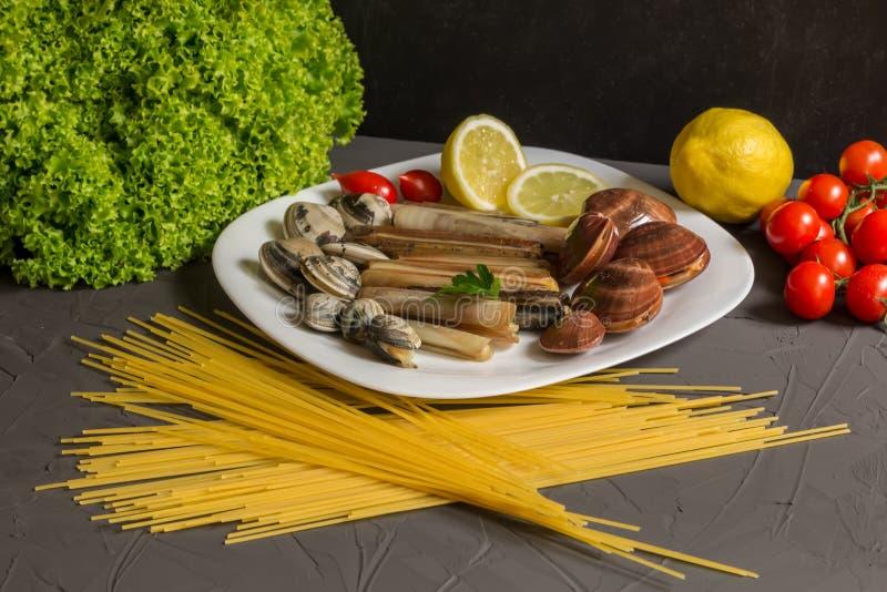 烹调的意粉和海鲜,蕃茄,大蒜,在灰色背景的荷兰芹新鲜的成份 免版税库存图片