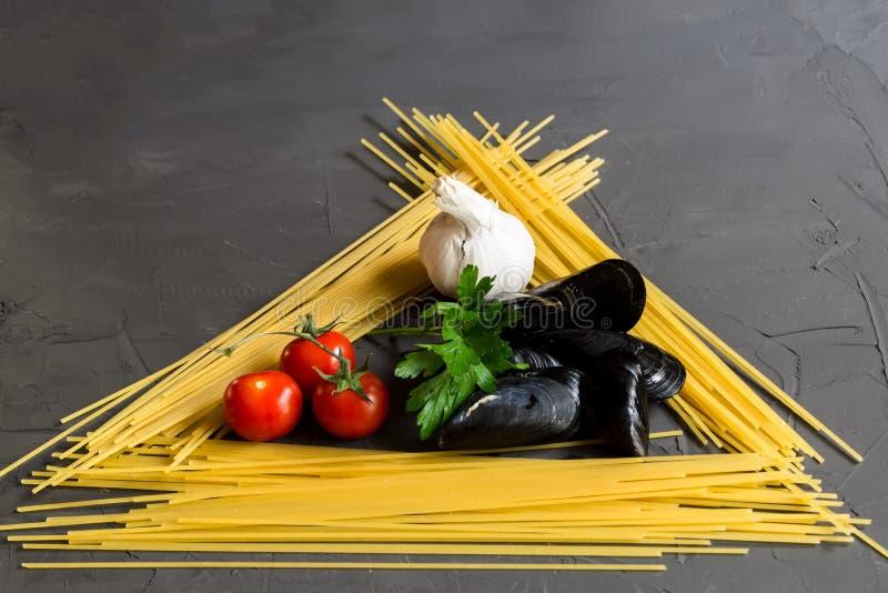烹调的意粉和淡菜,蕃茄,大蒜,在灰色背景的荷兰芹,顶视图,平的位置新鲜的成份 免版税库存图片