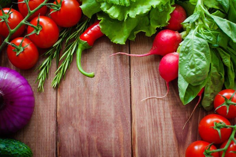 烹调的新鲜的成份在土气设置:沙拉,萝卜,葱,玉米,蕃茄,大蒜,红萝卜,黄瓜,胡椒 库存图片